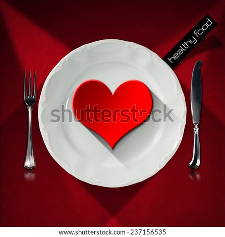 Healthy Food - Red Heart on the Plate. Red heart on the white plate with silver cutlery, fork and knife, on red velvet background with shadows. Concept of healthy food - stock photo