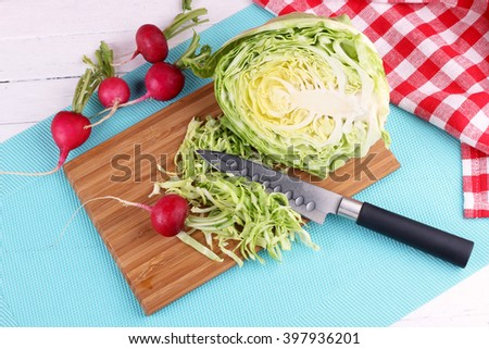 Healthy food salad ingredients top view on the white wooden table. Green fresh natural cabbage and radish slicing with knife. - stock photo