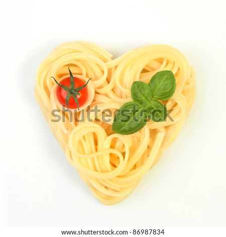 Healthy food, spaghetti in a heart shape with tomato and basil on a white background