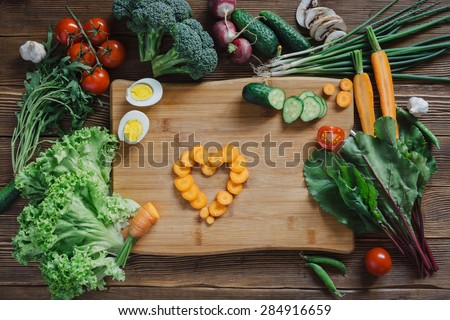 Healthy food with heart from carrot slices and tomato, arugula, beetroot, cucumber, onion, radish, mushrooms, garlic, broccoli, half, egg and peas ingredients on rustic wooden background, top view - stock photo