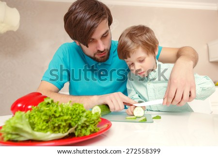 Healthy food. Young father in casual clothes teaching his small son how to cut cucumber  - stock photo