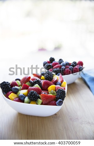 Healthy fresh fruit salad with strawberries, blackberries, mango, blueberries and kiwi. - stock photo