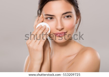 Healthy fresh girl removing makeup from her face with cotton pad. Beauty woman cleaning her face with cotton swab pad isolated on grey background. Skin care and beauty concept.