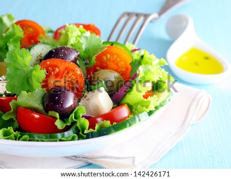 Healthy fresh Greek salad with olives and feta cheese nestling on a bed of crisp lettuce with tomato, closeup partial view of the dish