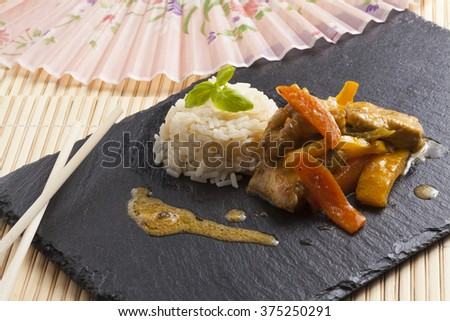 healthy fresh home made asian chicken rice dish on black slate plate - stock photo