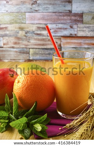 Healthy fresh pressed mango and orange juice with grains and mint for breakfast on wooden background - stock photo