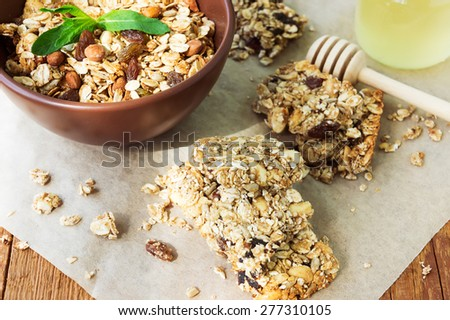 Healthy fruit and nuts muesli bars and a bowl of granola on vintage wooden background - stock photo