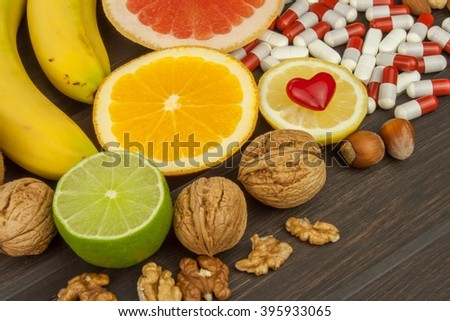 Healthy fruit for diet. Fresh fruit on dark wooden board. A healthy diet with vitamins. Artificial sports nutrition supplements. - stock photo