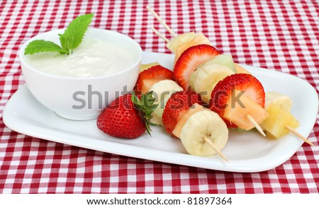 Healthy fruit kabobs with yogurt dip, garnished with fresh mint leaves. - stock photo