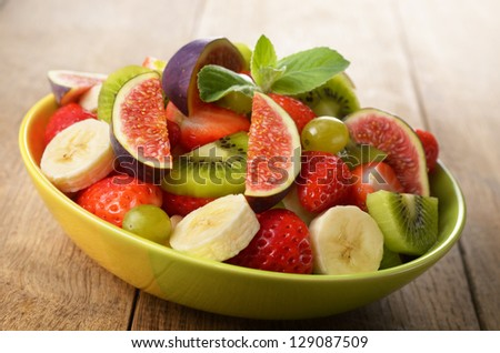 Healthy fruit mix salad on the kitchen table - stock photo