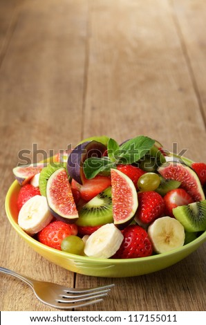 Healthy fruit mix salad on the kitchen table with copy-space - stock photo