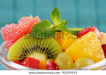 Healthy fruit salad over blue background closeup