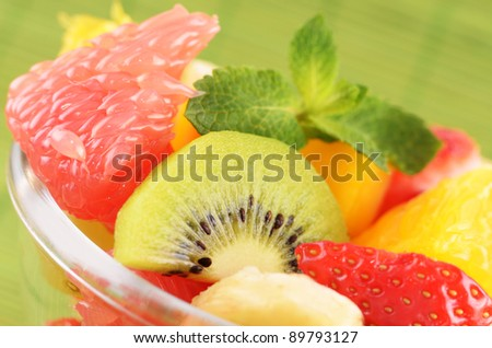 Healthy fruit salad over green background closeup