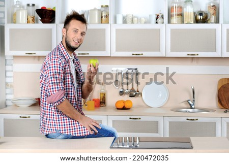 Healthy fruit. Young handsome man holding an apple while sitting and cooking in the kitchen and smiling at the camera - stock photo