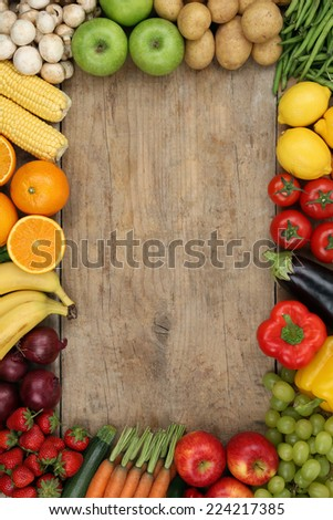 Healthy fruits and vegetables on wooden board with copyspace - stock photo