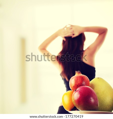 Healthy fruits with fitness girl in background