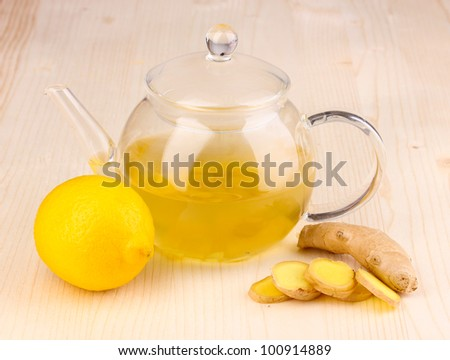 Healthy ginger tea in kettle with lemon on wooden background - stock photo