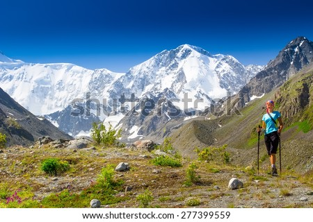 Healthy girl hiker with trekking poles to overcome difficulties in the mountains. Background of high mountains, glaciers. - stock photo