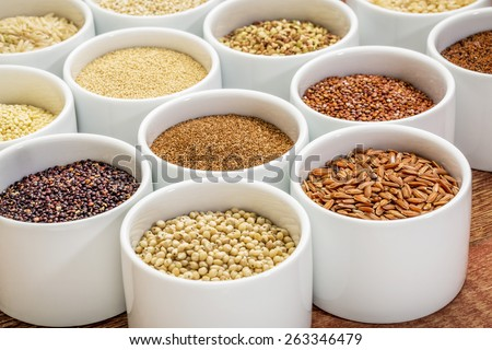 healthy, gluten free grains collection (quinoa, brown rice, millet, amaranth, teff, buckwheat, sorghum), small round bowls against rustic wood - stock photo