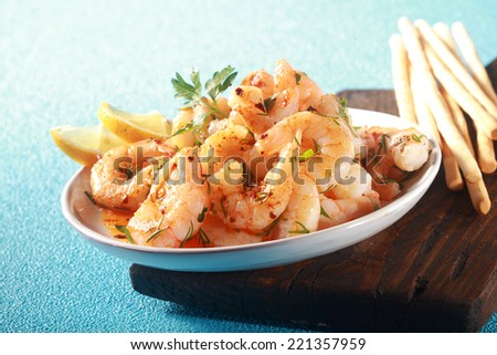 Healthy gourmet appetizer of grilled pink prawns or shrimp seasoned with olive oil and chopped fresh herbs and served with bread sticks on a blue textured table, low angle view - stock photo