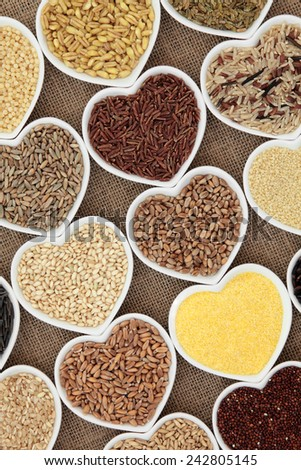 Healthy grain and cereal food selection in heart shaped porcelain bowls over hessian background. - stock photo