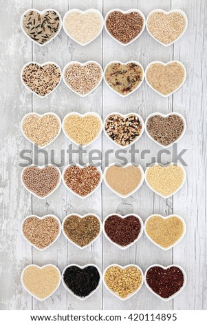 Healthy grain food selection in heart shaped porcelain bowls over distressed white wood background. - stock photo
