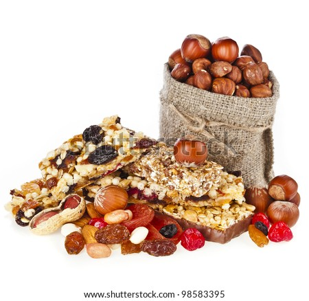 Healthy granola muesli  with a bag of hazelnuts isolated on white background - stock photo