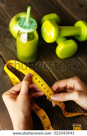 Healthy green detox, apple and dumbbells for slimming down. Woman with measuring tape before drinking fruit and vegetables smoothie for weight loss. Dieting and fitness nutrition concept. - stock photo
