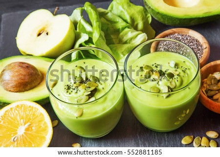Healthy green detox smoothie with avocado, kiwi, orange, apple and pumpkin seed and chia