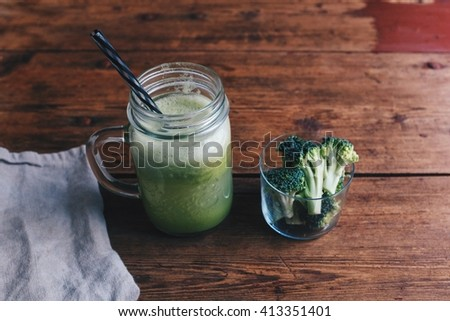 Healthy green drink; a mug of mixed broccoli, Apple and pine apple juice side with fresh cut broccoli in a small glass on the wooden table. - stock photo