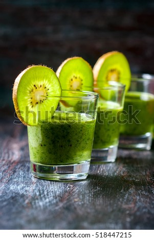 Healthy green smoothie from spinach and kiwi on a wooden table, selective focus