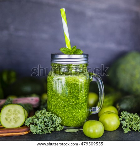 Healthy green smoothie in a mason jar mug on dark stone background. Vegetarian food.