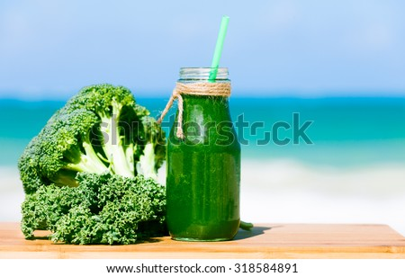 Healthy green smoothie with fresh kale and broccoli against a beach background - stock photo