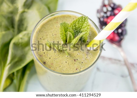 Healthy green smoothie with spinach and berries, selective focus