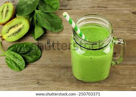 Healthy green smoothie with spinach and kiwi in a jar mug on wood, downward view - stock photo