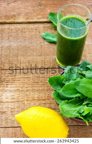 Healthy green smoothie with spinach and lemon on wooden background, with copyspace - stock photo