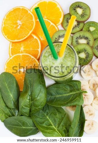 Healthy green smoothie with spinach, kiwi, bananas and oranges in a jar with green and yellow straws on a white table, selective focus - stock photo