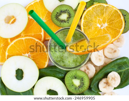 Healthy green smoothie with spinach, kiwi, bananas, apples and oranges in a jar with green and yellow straws on a white table, selective focus - stock photo