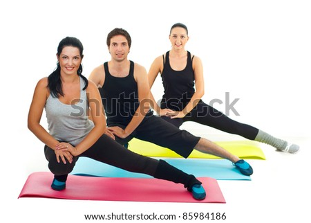 Healthy group of three people doing fitness exercises on colorful mats - stock photo