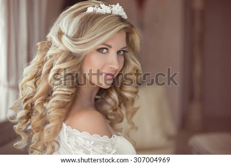 Healthy hair. Beautiful smiling girl bride with long blonde curly hairstyle and bridal makeup. Wedding indoor portrait.  - stock photo