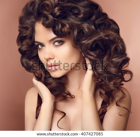 Healthy hair. Makeup. Beautiful brunette girl model with long curly hairstyle. Elegant lady with make-up, eye shadow.  - stock photo
