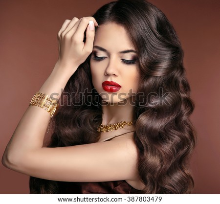 Healthy hair. Makeup. Beautiful brunette girl with long wavy hairstyle. Red lips. Elegant lady with jewelry. - stock photo
