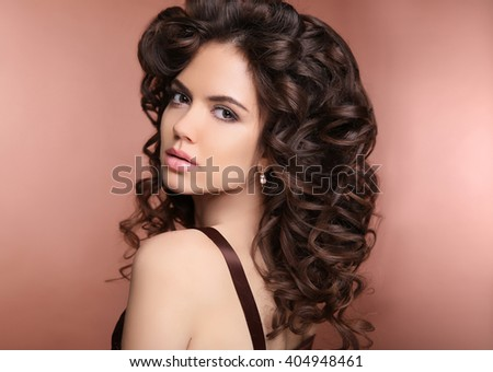 Healthy hair. Makeup. Beautiful brunette woman with long curly hairstyle. Elegant lady with jewelry. - stock photo