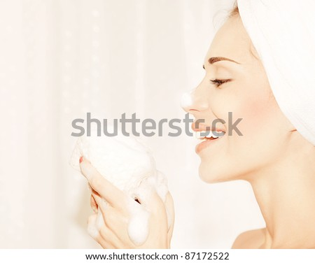 Healthy happy girl taking bath, profile portrait of a beautiful young female cleaning face skin, hygiene and day spa - stock photo