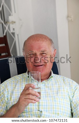 Healthy happy pensioner relaxing in a comfortable chair enjoying a glass of fresh pure drinking water