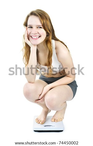 Healthy happy young woman crouching on bathroom scale isolated on white - stock photo
