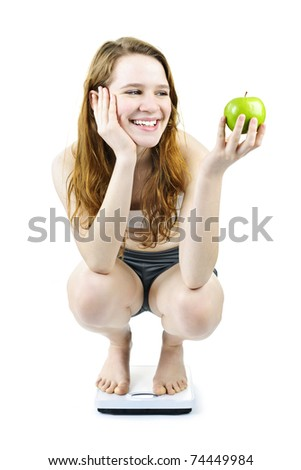 Healthy happy young woman holding apple on bathroom scale isolated on white - stock photo