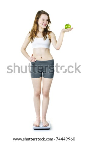 Healthy happy young woman holding green apple standing on bathroom scale - stock photo
