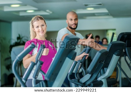 Healthy Heart. Workout in the gym in the cardio room. Two athletes engaged in the simulator and the gym  showing thumbs up at the camera - stock photo