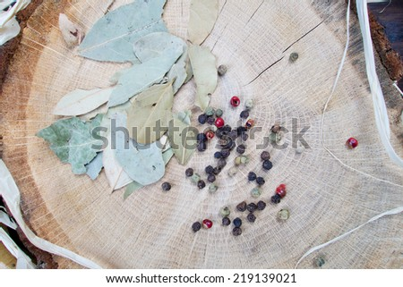 Healthy herbs - Bay leaves and black and red pepper on wooden board